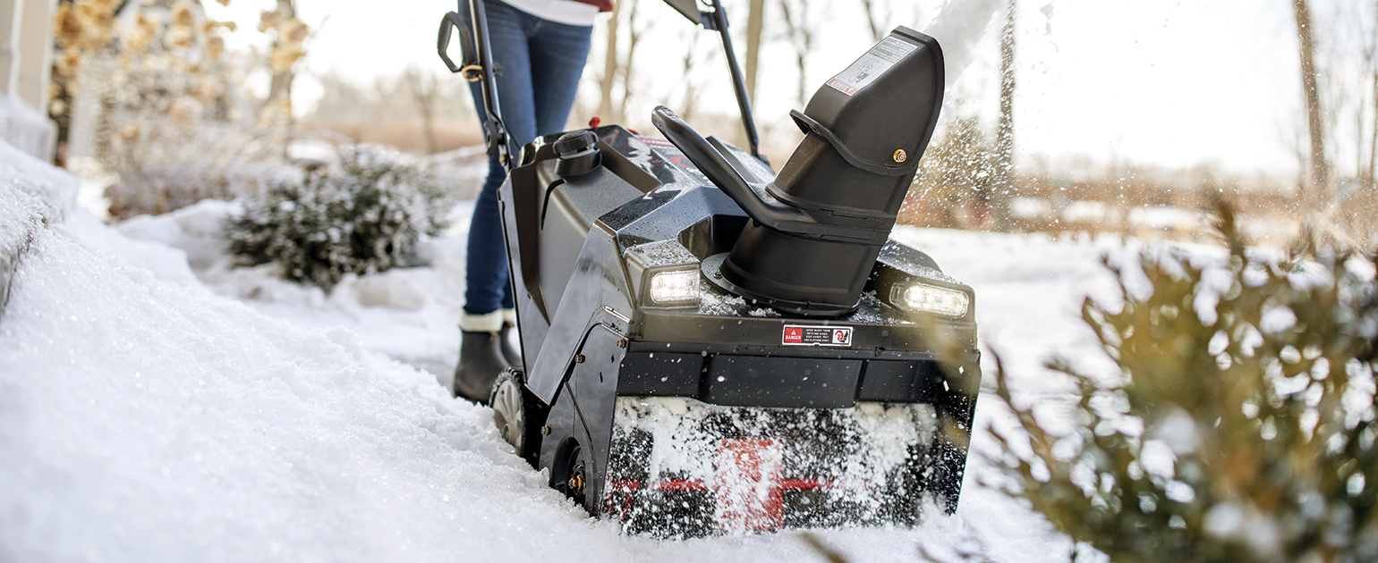 woman using single-stage snow blower on walkway
