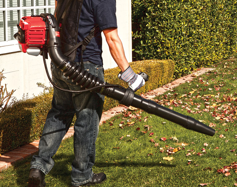 man using backpack leaf blower to blow leaves off lawn