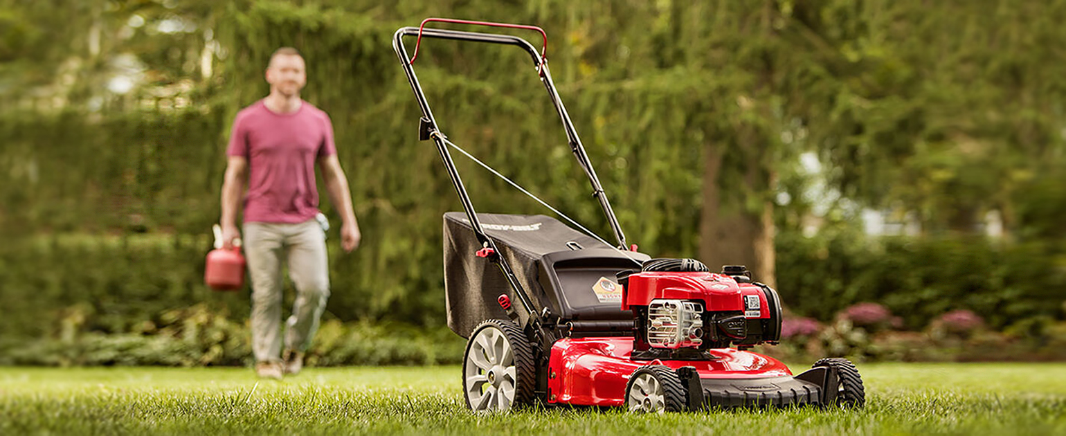picture of man walking with jerry can towards mower