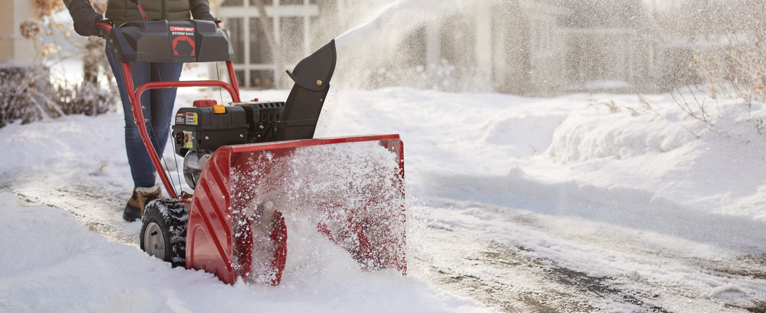 two-stage snow blower clearing driveway