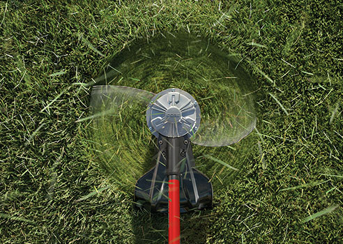 top view of string trimmer cutting an area of grass