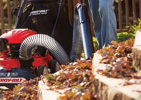 man cleaning up leaves on steps using Chipper shredder Vacuum