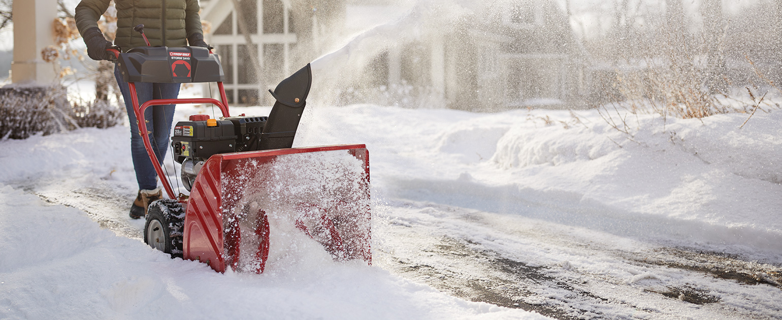 person plowing driveway with two stage snow blower
