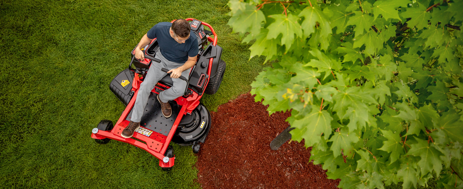 top view of man mowing around a tree with zero-turn mower