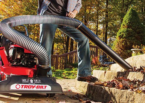 Man cleaning leaves on steps with Troy-Bilt Chipper Shredder Vacuum