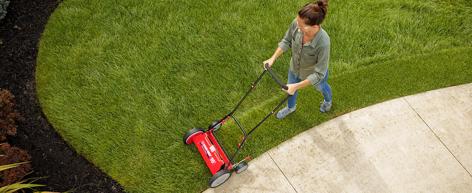woman using a reel mower on her lawn
