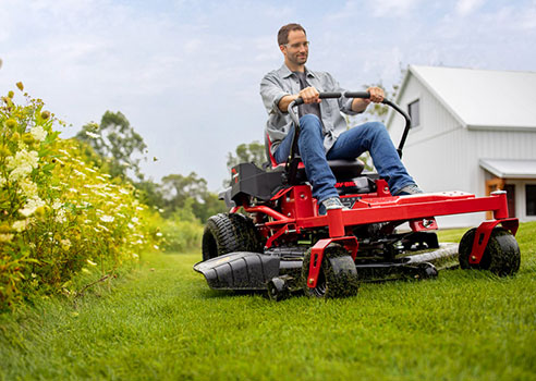 man riding troy-bilt zero-turn riding lawn mower on yard