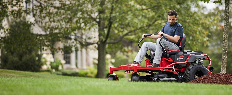 zero-turn mower cutting around garden bed