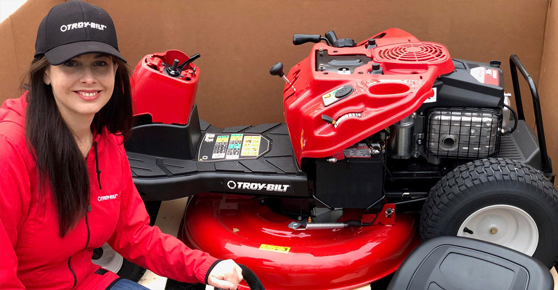 Niki Jabbour in front of new Lawn Mower in the box